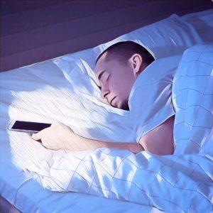 Hombre durmiendo  con el teléfono móvil en la cama